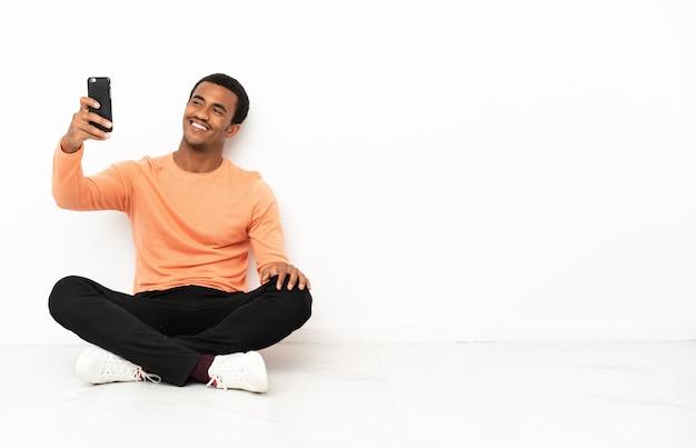 Афро-американский мужчина сидит на полу над изолированной стеной copyspace, делая селфи