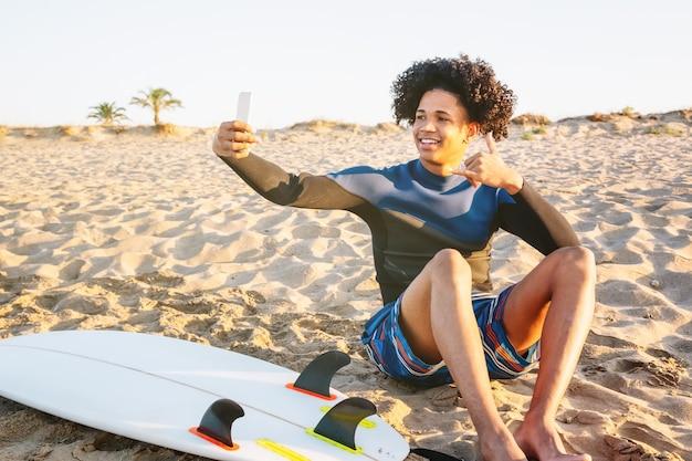 サーフボードで砂の上に座っているアフリカ系アメリカ人の男性がスマートフォンで写真を撮る
