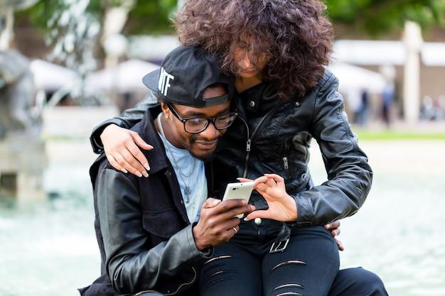 Афро-американский мужчина сидит с подругой у фонтана, показывает сообщение на мобильном телефоне или ищет информацию