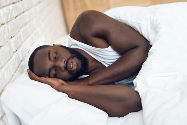 Афро-американский мужчина спит в постели.