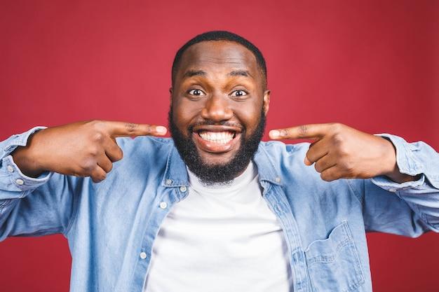 アフリカ系アメリカ人の男の笑顔。赤い背景に分離された歯科医療。