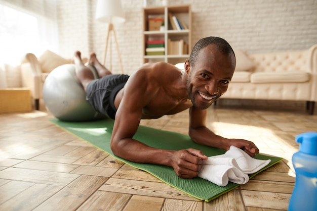 African american man smile performs plank.