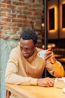 コーヒーを飲みながら笑っているアフリカ系アメリカ人の男
