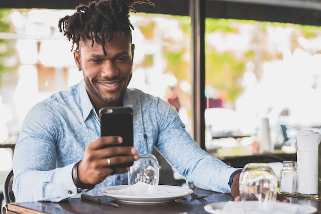 African american man smiling while using a mobile phone at a restaurant.