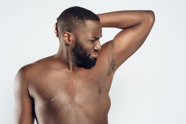Афро-американский мужчина нюхает вонючие подмышки.