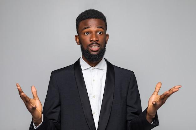 Афро-американский мужчина, стоящий в костюме с вытянутыми руками, не уверен