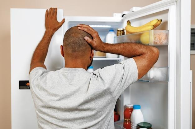 オープン冷蔵庫の前に立って食べ物を選ぶアフリカ系アメリカ人の男