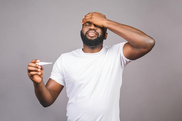 アフリカ系アメリカ人の男は、温度計を使用して、孤立した灰色の背景、病気、発熱、インフルエンザ、風邪、ウイルスの病気の上に立っています。