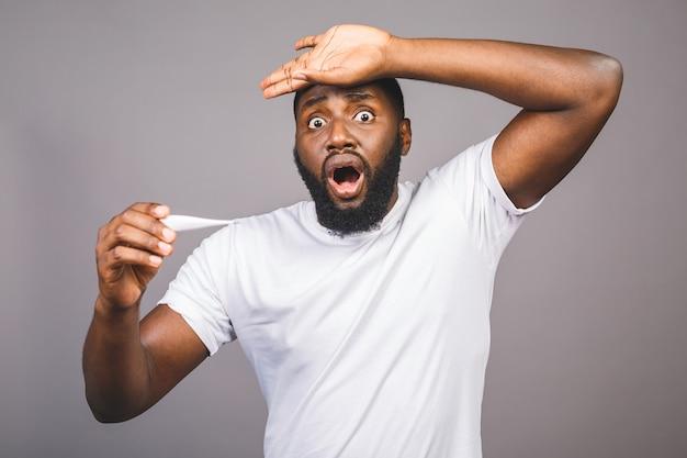 孤立した灰色の背景の上に立っているアフリカ系アメリカ人の男温度計を使用して病気や発熱、インフルエンザや風邪、ウイルスの病気のために額に触れる。