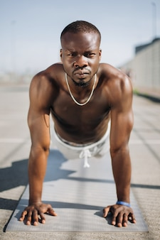 African american man stands on his arms on the ground doing push-ups