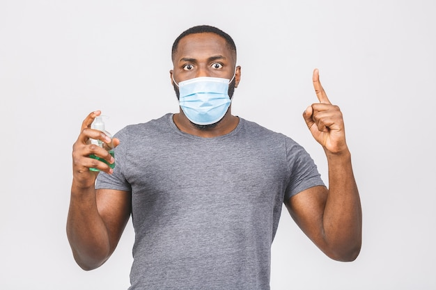 African american man in sterile face mask. holding bottle with antibacterial sanitizer.