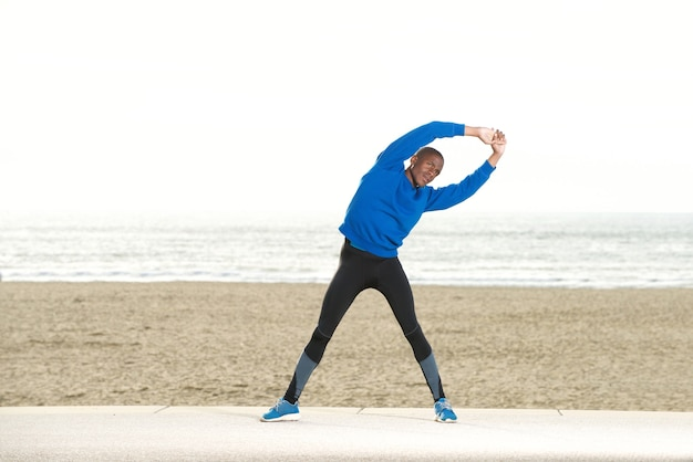 African american man stretching muscles at the beach