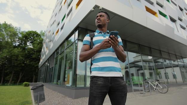 スマートフォンを使用してアフリカ系アメリカ人の学生が背景に現代の家を屋外に立っているアフリカ人男性だけが画面に触れている