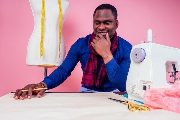 Афро-американский мужчина ателье швеи стильная мужская модель дизайнер одежды процесс создания новой коллекции платьев на розовом фоне в студии copyspace