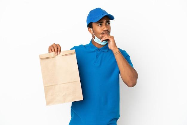 白い背景で隔離の持ち帰り用食品の袋を取り、見上げるアフリカ系アメリカ人の男