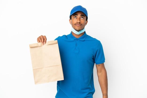 흰색 배경에 격리된 테이크아웃 음식 한 봉지를 들고 올려다보는 아프리카계 미국인 남자