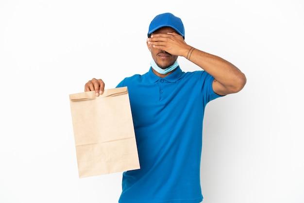 Афро-американский мужчина, принимая мешок еды на вынос, изолированные на белом фоне, закрывая глаза руками. не хочу что-то видеть