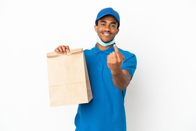 Афро-американский мужчина берет сумку еды на вынос, изолированную на белом фоне, делает приближающийся жест