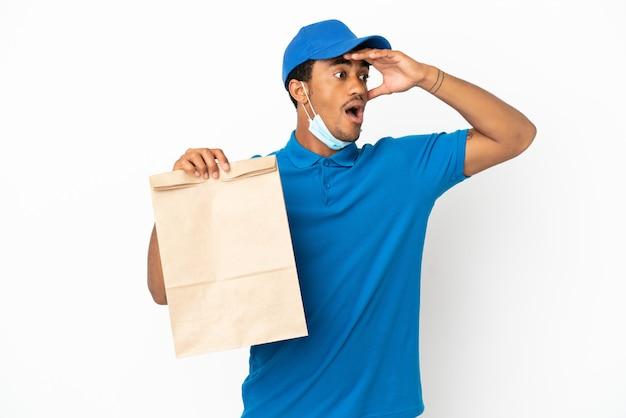 측면을 보면서 깜짝 제스처를 하 고 흰색 배경에 고립 된 테이크 아웃 음식 가방을 복용하는 아프리카 계 미국인 남자