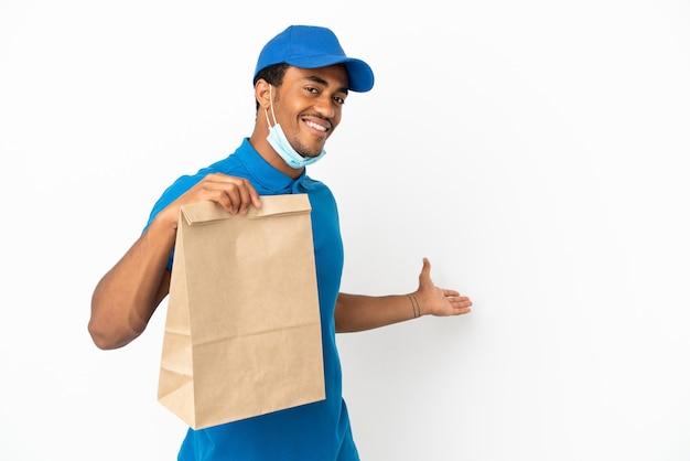 白い背景で隔離の持ち帰り用食品の袋を取っているアフリカ系アメリカ人の男は、来て招待するために手を横に伸ばします