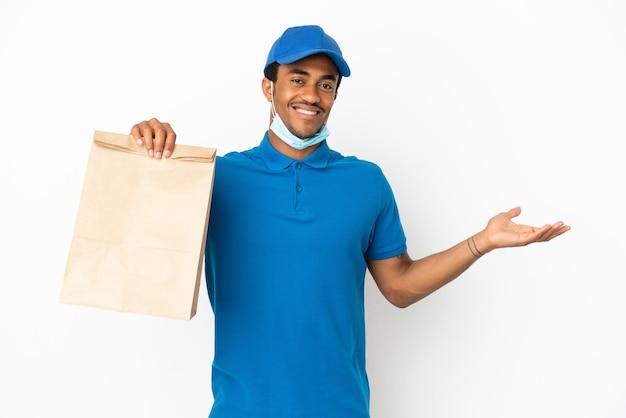 Афро-американский мужчина берет сумку с едой на вынос на белом фоне, протягивая руки в сторону, чтобы пригласить приехать