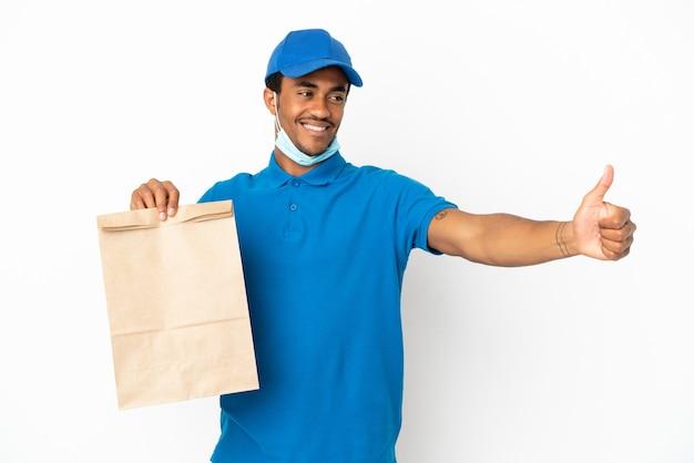 親指を立てるジェスチャーを与える白い背景で隔離の持ち帰り用食品の袋を取るアフリカ系アメリカ人の男