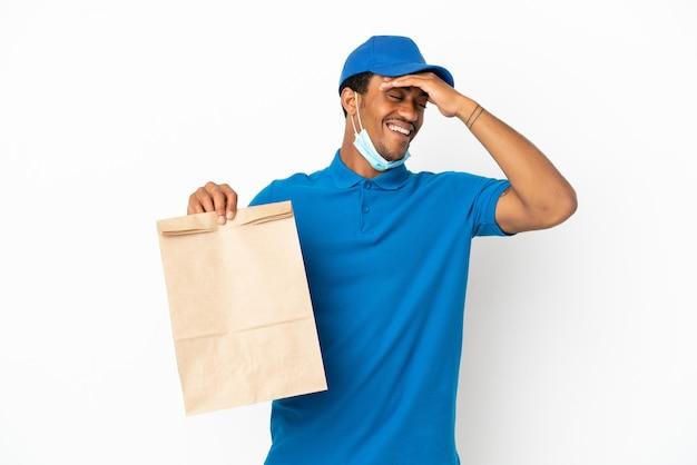 흰색 배경에 격리된 테이크아웃 음식 한 봉지를 들고 있는 아프리카계 미국인 남자는 무언가를 깨닫고 해결책을 의도하고 있습니다