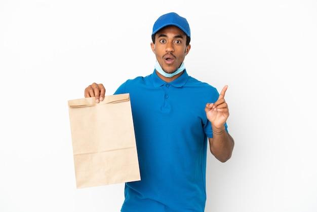 指を持ち上げながら解決策を実現しようと意図して白い背景で隔離の持ち帰り用食品の袋を取っているアフリカ系アメリカ人の男