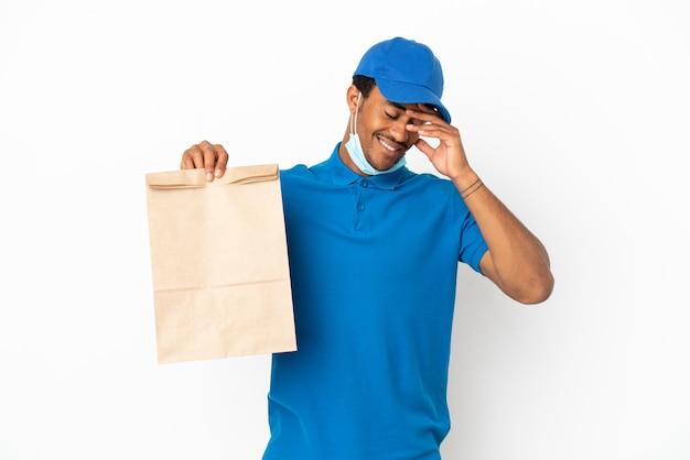 흰색 배경 웃음에 고립 된 테이크 아웃 음식 가방을 복용하는 아프리카 계 미국인 남자