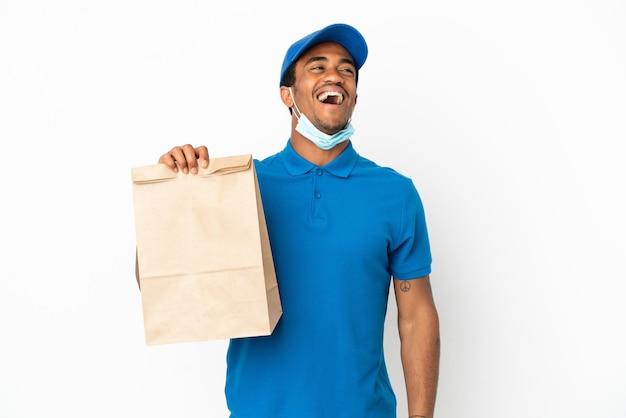 笑って白い背景で隔離の持ち帰り用食品の袋を取っているアフリカ系アメリカ人の男