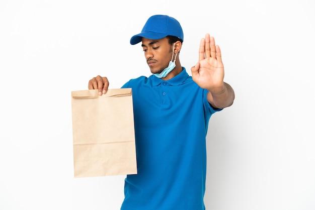 Афро-американский мужчина берет сумку еды на вынос, изолированную на белом фоне, делает стоп-жест и разочарован