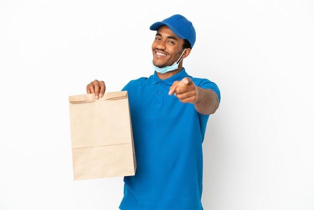 Афро-американский мужчина берет сумку еды на вынос, изолированную на белом фоне, указывая спереди с счастливым выражением лица