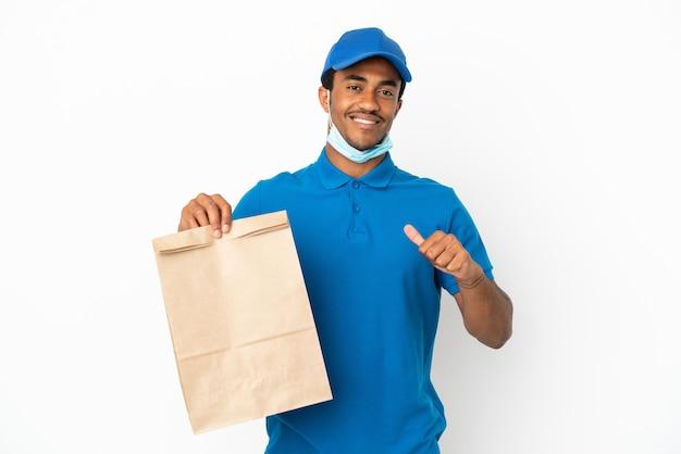 誇りと自己満足の白い背景で隔離の持ち帰り用食品の袋を取っているアフリカ系アメリカ人の男