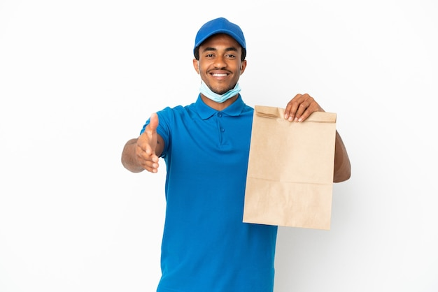 Афро-американский мужчина берет сумку с едой на вынос на белом фоне, пожимая руку для закрытия хорошей сделки