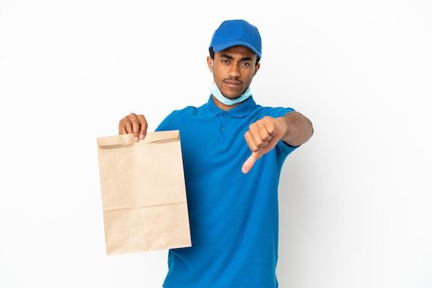 흰색 배경에 격리된 테이크아웃 음식 한 봉지를 들고 부정적인 표정으로 엄지손가락을 아래로 내리는 아프리카계 미국인 남자