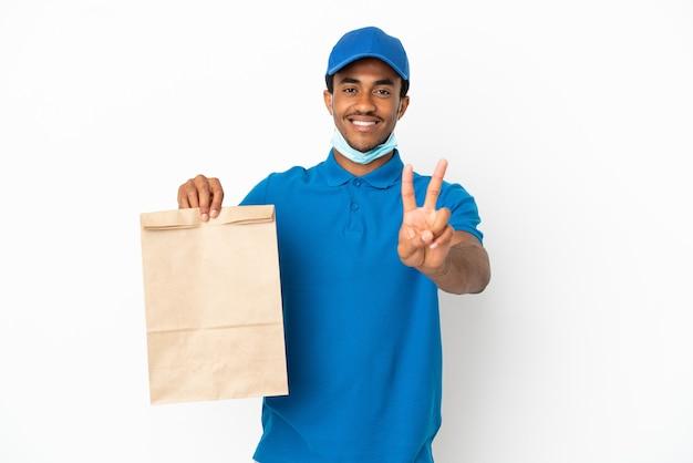 Афро-американский мужчина берет сумку еды на вынос, изолированную на белом фоне, улыбается и показывает знак победы
