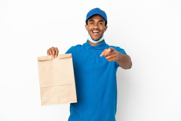 테이크 아웃 음식 가방을 복용 아프리카 계 미국인 남자는 놀라게하고 앞을 가리키는 흰색 배경에 고립