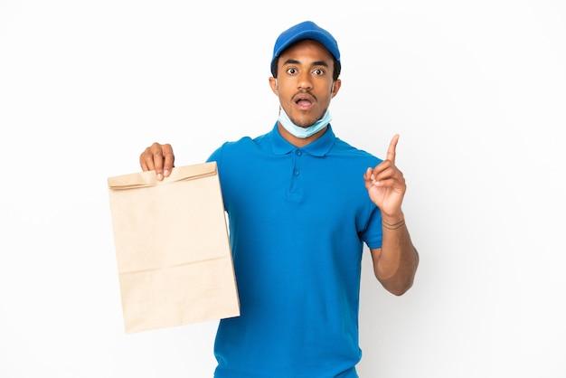 손가락을 가리키는 아이디어를 생각하는 흰색 배경에 고립 된 테이크 아웃 음식 가방을 들고 아프리카 계 미국인 남자
