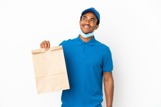 見上げながらアイデアを考えて白い背景で隔離の持ち帰り用食品の袋を取っているアフリカ系アメリカ人の男