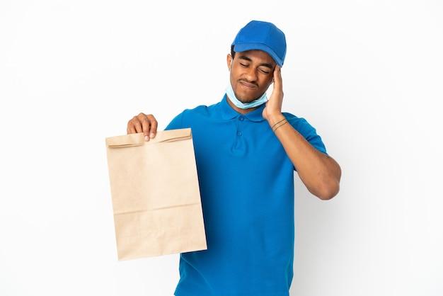 두통으로 흰색 배경에 고립 된 테이크 아웃 음식 가방을 들고 아프리카 계 미국인 남자