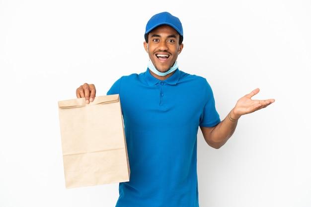 Афро-американский мужчина берет сумку еды на вынос, изолированную на белом фоне с шокированным выражением лица