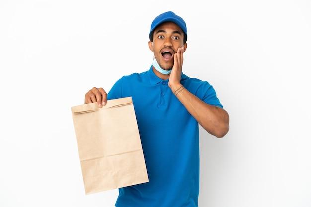 놀라움과 놀란 표정으로 흰색 배경에 고립 된 테이크 아웃 음식 가방을 들고 아프리카 계 미국인 남자