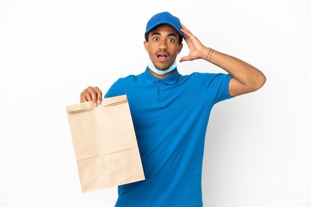 Афро-американский мужчина берет сумку еды на вынос, изолированную на белом фоне с удивленным выражением лица