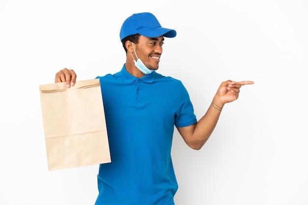 白い背景で隔離の持ち帰りの食べ物の袋を取っているアフリカ系アメリカ人の男