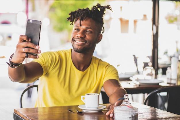 Афро-американский мужчина, делающий селфи с мобильным телефоном, сидя в кафе.