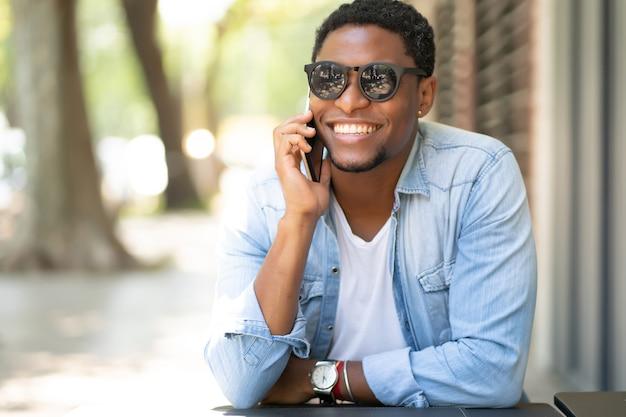 커피 숍에 앉아있는 동안 전화로 얘기하는 아프리카 계 미국인 남자