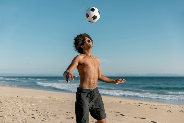 African american man tossing ball up on beach