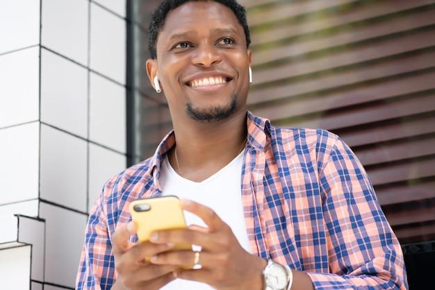 거리에 상점 창에 앉아있는 동안 그의 휴대 전화를 사용하는 아프리카 계 미국인 남자. 도시 개념.