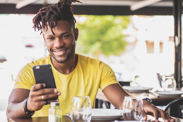 African american man using his mobile phone while sitting in a restaurant.