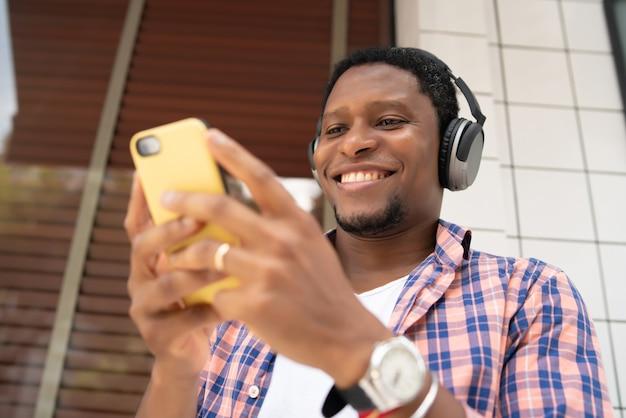 路上で屋外に立っている間彼の携帯電話を使用してアフリカ系アメリカ人の男